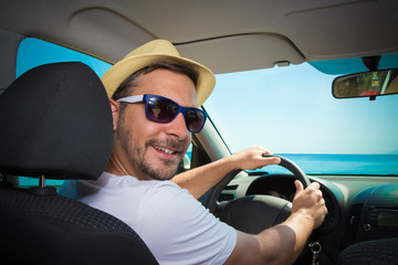Portrait of tourist guy in car. Travel and summer vacation concepts.