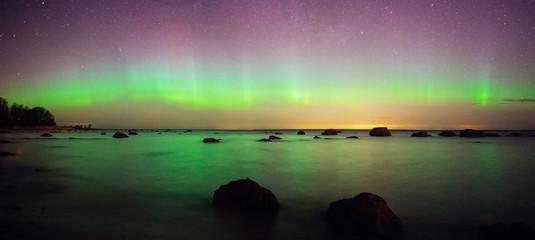 Starry sky and aurora borealis over sea coast