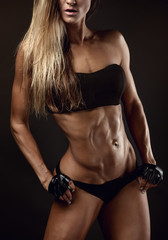 Nice sexy fitness woman showing abdominal muscles
