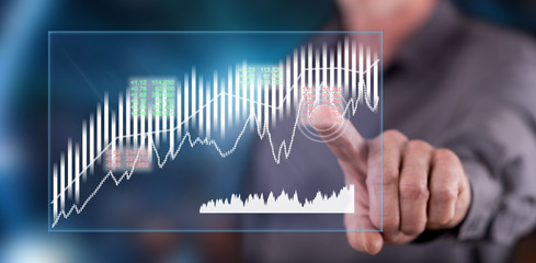 Man touching a stock market concept on a touch screen