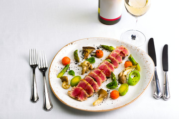 Salad of tuna and vegetables with a glass of wine and a bottle of wine on a white tablecloth, studio light