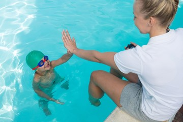 Female trainer giving high five to boy