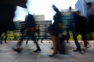 Blurred motion of businessmen and businesswomen commuting to work during busy rush hour in Tokyo, Japan