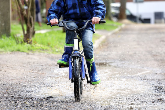 The boy on the bike riding on the puddles