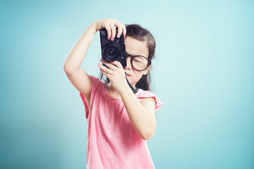 Portrait of cute asian little girl taking picture with retro camera in the studio on vintage mint green background.
