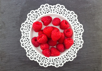 Fresh Red Raspberries on a white artistic plate / Red Fresh Raspberries on a white artistic plate with cookies, rosemary, chocolate and cream in the background.