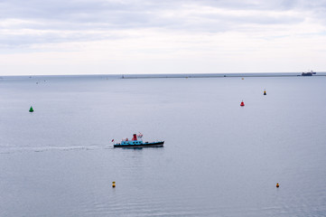 A solitary boat leaves the harbor of Plymouth, Cornwall, UK