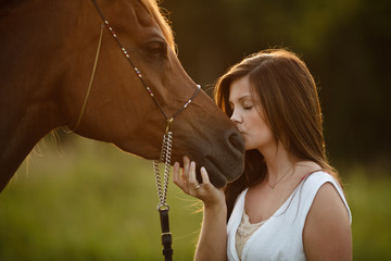 Woman kissing horses muzzle