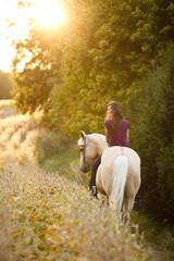 Woman riding horse through a meadow