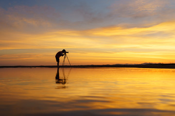 Silhouette Tourist take photo beautiful seascape at sunset in Thailand.