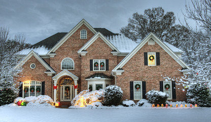 Beautiful brick estate home exterior in snow decorated for the holidays