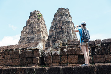 Woman taking picture to Angkor wat temple.