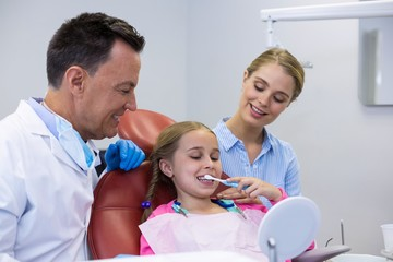 Dentist assisting young patient while brushing teeth
