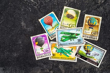Set of randomly lying postage stamps printed in Mongolia shows balloons and airplanes, series, circa 1976-1982. Copy space for your text on a dark black cement background.