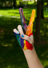 Rainbow painted hand making a peace sign with the fingers and a shallow depth of field