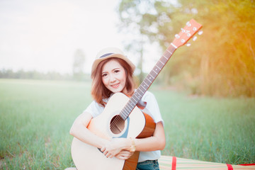 portrait of a happy young woman asia playing guitar outdoors