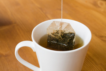 Hot tea with tea bag in white cup on wooden table in winter to keep warm