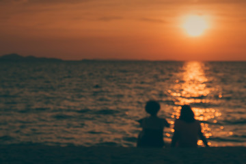 silhouette and blur of two middle-aged happy women sitting on the beach talking about old day and watching the sunset on the horizon. emotional and friend relation concept.