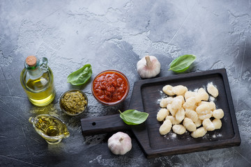 Black wooden serving board with raw potato gnocchi and cooking ingredients, grey stone background, horizontal shot