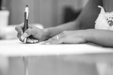 foto b/n della mano di una sposa che firma con una penna un documento