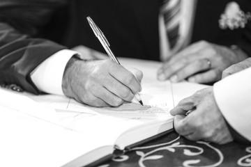 foto b/n di una mano che firma con una penna un  atto di matrimonio mentre il prete lo tiene