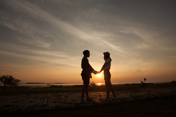 Romantic couple at colorful sunset on background