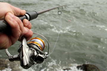 Close-up of fishing reel in hand with the ocean in the background.
