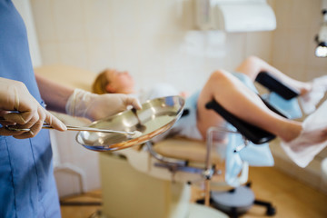 Red hair female doctor holding tool in steel basin in front of the female patient on gynecological chair. Close up