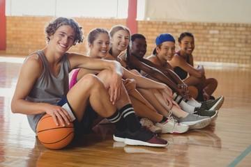 High school kids sitting indoors in basketball court