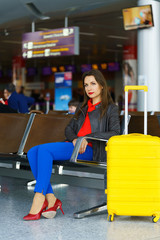 Woman in bright clothes with yellow suitcase sits at the airport
