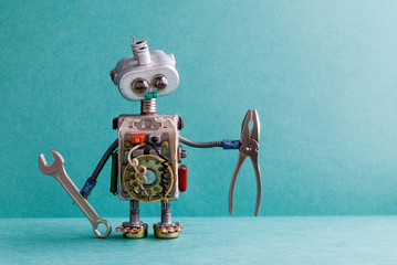 Creative design electrician robot with hand wrench pliers. Funny toy mechanic character lamp bulb eyes head, electric wires, capacitors vintage resistors. Green paper background copy text