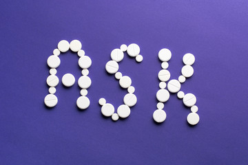Word ASK made of white pills on purple background