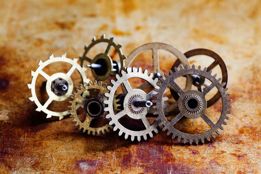 Antique clock mechanism steampunk style cogs gears wheels macro view. Vintage rusty metal surface background, shallow depth of field