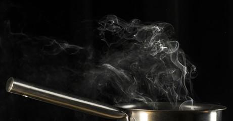 Boiling pot on black background