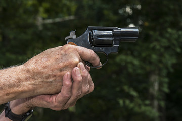 Hands aiming a 38 Detective Special pistol handgun