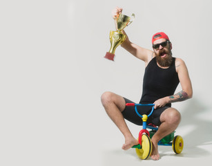 bearded happy man holds gold champion cup on bicycle toy