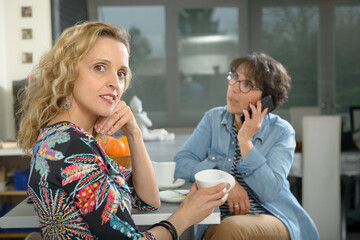 two women sitting at table in kitchen and drinking coffee.
