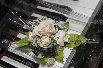 Floral wrist corsage on piano keys