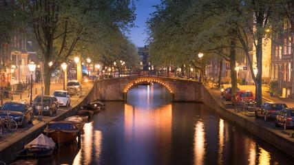Fotobehang Oude gebouw Beleuchtete Brücke mit Spiegelung in Amsterdam