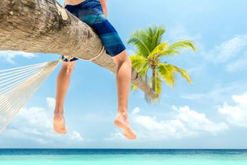 Junge sitzt auf Kokospalme am Strand