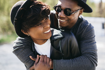 A beautiful and stylish young african couple in sunglasses and hats embracing on a outdoor of summer.