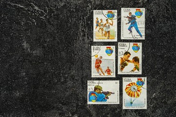 Set of randomly lying postage stamps printed in Cuba shows sportsmen, devoted to 4 Spartakiad,  series, circa 1977, on a dark black cement background.