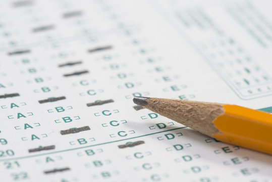 Close up of a standardized test form with a pencil resting on it with a shallow depth of field