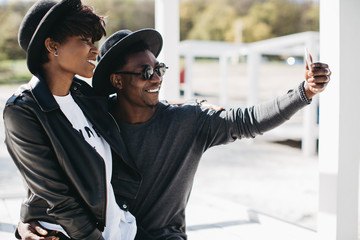 A beautiful and stylish young african couple in sunglasses and hats embracing and making selfie on a outdoor of summer.