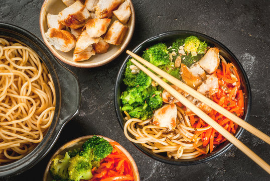 Healthy eating, diet. Buddha bowl hot salad in Asian style: noodles with soy sauce, spicy carrots, chicken, broccoli. On black stone table, with chopsticks and ingredients for cooking. Top view