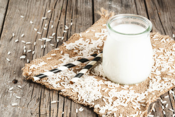 Rice milk, with rice grains. On a rustic wooden table. With a striped tube for drinking. Copy space