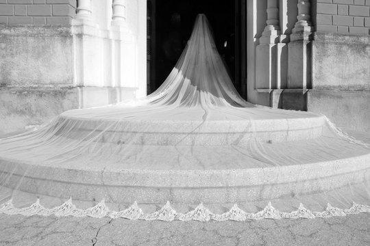 Sposa con velo in primo piano sulle scale entra in chiesa per il suo matrimonio di nozze