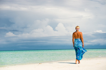 Rear view of blonde woman in blue sarong standing on the white sand beach.Copy space