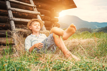 Boy in straw hat lies in hay near the barn