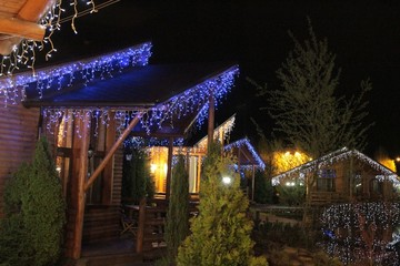 Wooden cottage at night. The village is decorated with beautiful lights. Illuminations. Spring night in the village.